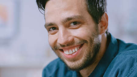Portrait of Handsome Young Man Using Laptop Computer at Home, Watching into the Camera. Happy Hispanic Man Smiles.