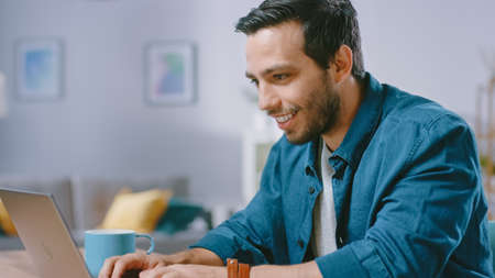 Portrait of Handsome Young Man Using Laptop Computer at Home, Watching and Smiling at a Content. Cozy Modern Flat done in Scandinavian Style.