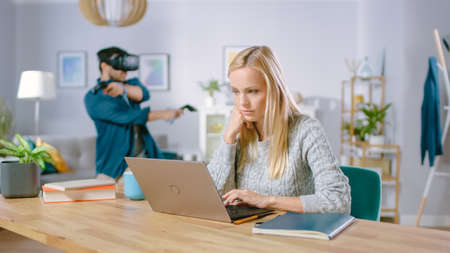 Beautiful Concentrated Woman Works on a Laptop at Her Desk, Behind Her Boyfriend Wearing Virtual Reality Headset Plays in Video Game with Controllers