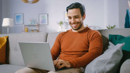 Cheerful Young Man at Home Sitting on a Sofa Holds Laptop on His Lap, Browses Through the Internet, Social Networks, Does e-Shopping.