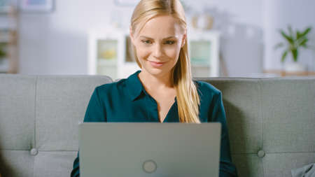Beautiful Young Woman Relaxes on a Sofa at Home, Uses Laptop, Browses through Internet, Watches Funny Videos and Does e-Shopping. Archivio Fotografico