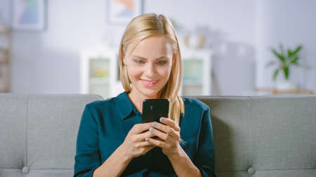 Beautiful Blonde Woman Uses Mobile Phone while Sitting on a Sofa at Home. Smiling Happy Woman Uses Smartphone for Browsing through Internet, Social Networks and Watching Videos.