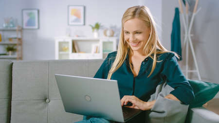 Beautiful Young Woman Relaxes on a Sofa at Home, Uses Laptop, Browses through Internet, Watches Funny Videos and Does e-Shopping.