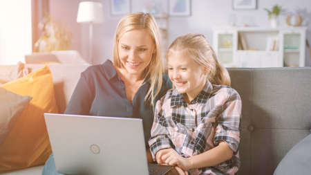 Beautiful Young Mom and Her Cute Little Daugther Use Laptop while Sitting on a Sofa at Home. Family Spending Time Together Watching Videos and Cartoons on Computer. Shot with Warm Sun Light.