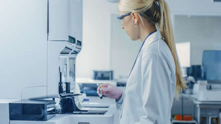 Female Research Scientist Places Test Tube with Blood Sample Into Medical Analyzing Equipment. Scientist Works in Modern Pharmaceutical Laboratory. Banco de Imagens