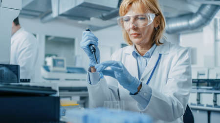 Female Research Scientist Uses Micro Pipette while Working with Test Tubes. People in Innovative Pharmaceutical Laboratory with Modern Medical Equipment for Genetics Research.
