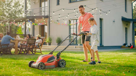 Good Father Teaches Son How to Use Walk Behind Lawn Mower, They Push it Together, Cutting Grass. Family Spending Time Together on a Sunny Day.