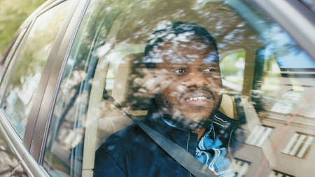 Handsome Young Black Man Rides on a Passenger Seat of a Car, Looks out of the Window. Big City View Reflected in Window. Camera Mounted outside the Car. Stock fotó