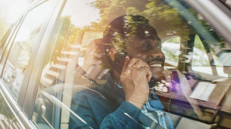 Handsome Young Entrepreneur Traveling on a Passenger Seat of a Car Makes a Phone Call, Talks with Clients or Relatives. Camera Shot from Outside the Vehicle.
