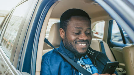 Handsome Entrepreneur Traveling on a Passenger Seat of a Car, Uses Smartphone and Smiles. Camera Shot from Outside the Vehicle. Stock fotó