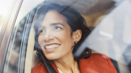 Beautiful Happy Woman Rides on a Passenger Seat of a Car, Looks in Wonder at Big City View. Camera Mounted outside Moving Car. Stock fotó