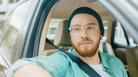 Stylish Young Man Rides on a Passenger Seat of a Car and Looks in Open Window in Wonder at the Big City. Camera Mounted outside Moving Car.
