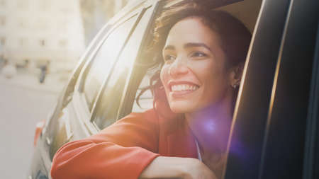 Happy Beautiful Woman Riding on a Back Seat of a Car, Looks out of the Open Window in Wonder of the Big City. Traveling Girl Experience Magic of the World. Shot Made from Outside the Vehicle.