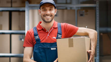 Portrait of Handsome Warehouse Worker in Uniform Holds Cardboard Box Package and Smiles.
