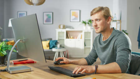 Portrait of the Focused Young Man Working on a Personal Computer while Sitting at His Desk. In the Background Cozy Living Room.