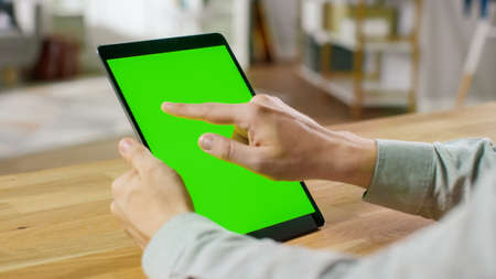 Man Using Hand Gestures on Green Mock-up Screen Digital Tablet Computer in Portrait Mode while Sitting at His Desk. In the Background Cozy Living Room. 写真素材