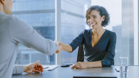 Beatiful Young Businesswoman Talks with a Potential Business Partner and Shakes Hands When them come to a Agrement. Strong Independent Woman in Business Situation.