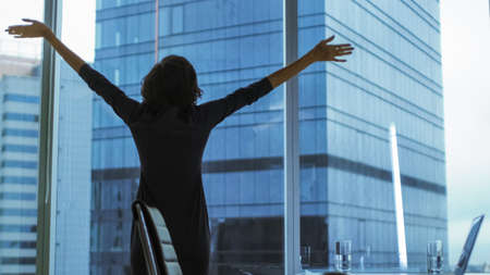 Back View of the Businesswoman Standing in Her Office Stretching, Raising Arms, Celebrating Success while Looking out of Window with Cityscape View. 免版税图像