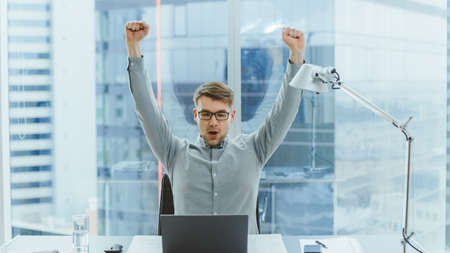 Handsome Young Businessman Sitting at His Desk Using Laptop in the Office Raises Hands and Celebrates Impressive Fiscal Results. In the Background Window with Cityscape View. 版權商用圖片