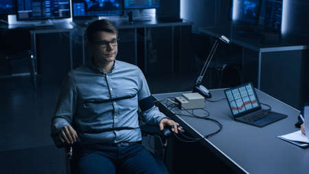 Young Handsome Suspect During Interrogation Undergoes Lie Detector Polygraph Test, Connected to the Machine He Answers Yes or No Questions Which Computer Records and Shows if  Lying.