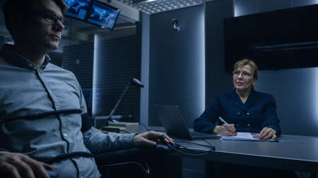 Female Special Agent Conducts Lie Detector Polygraph Test on a Young Suspect. Expert Examiner Questions Accused in Interrogation Room. Computer Measures Physiological indices.