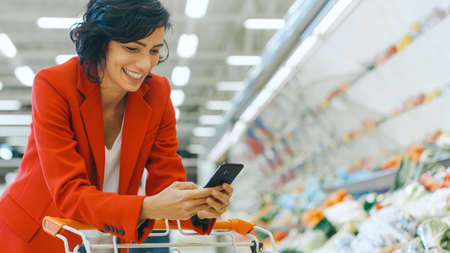 At the Supermarket: Beautiful Smiling Woman Uses Smartphone, Leans on Shopping Cart in the Fresh Produce Section of the Store. In the Big Mall Woman Browsing In Internet on Her Mobile Phone.