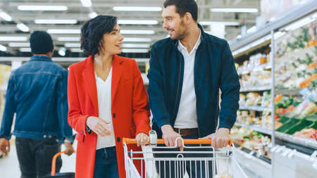 At the Supermarket: Happy Young Couple Walks Through Fresh Produce Section of the Store, They Talk, Man Embraces Woman Lovingly.