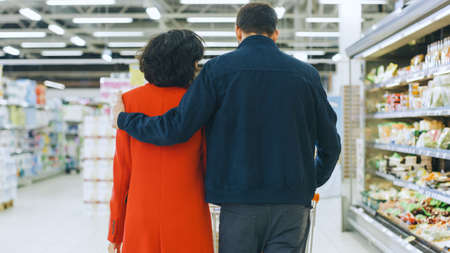 At the Supermarket: Happy Young Couple Walks Through Fresh Produce Section of the Store, Man Embraces Woman Lovingly. Back View Shot. Stockfoto