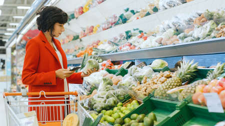 At the Supermarket: Shot of a Beautiful Young Woman Walks Through Fresh Produce Section, Chooses Broccoli and Puts them in Her Shopping Cart. Reklamní fotografie