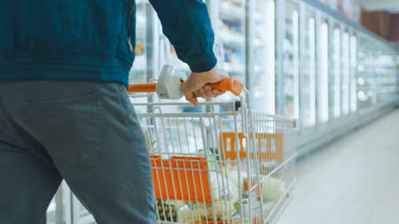 Shot At the Supermarket: of the Man Pushing Shopping Cart Full of Products Through Frozen Goods and Dairy Section of the Store.