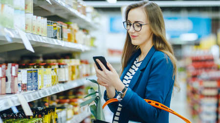 At the Supermarket: Beautiful Young Woman Uses Smartphone While Browsing through the Canned Goods Section of the Store. She Checks Her Shopping List and Holds Shopping Basket.