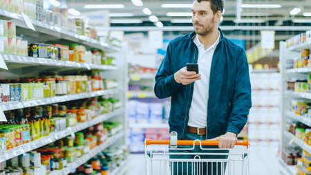 At the Supermarket: Handsome Man Uses Smartphone and Looks at Nutritional Value of the Canned Goods. Hes Standing with Shopping Cart in Canned Goods Section.