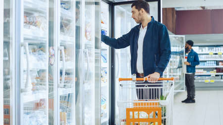 At the Supermarket: Handsome Man Pushes Shopping Card and Browses for Products in the Frozen Goods Section. Man Opens the Fridge Door and Takes Frozen Vegetables. Other Customer Shopping in Background