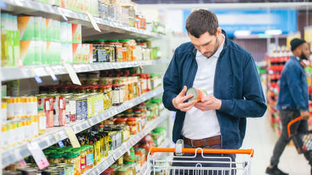 At the Supermarket: Handsome Man Uses Smartphone and Looks at Nutritional Value of the Canned Goods. Hes Standing with Shopping Cart in Canned Goods Section. Stock fotó