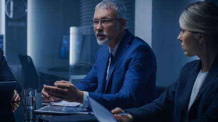 Chairman of the Board of Directors Making a Speech to His Professional Colleagues thus Saving Corporation in Emergency Situation. In the Background Monitors with Various Data. Stock Photo