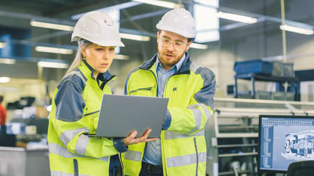 Male Industrial Worker and Female Chief Mechanical Engineer in Walk Through Manufacturing Plant while Discuss Factorys New Project and Using Laptop. Facility Has Working Machinery.