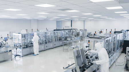 Sterile High Precision Manufacturing Laboratory where Scientists in Protective Coveralls Turn on Machninery, Use Computers and Microscopes, doing Pharmaceutics, Biotechnology and Semiconductor