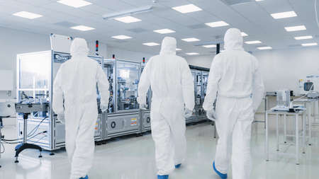 Back Shot of a Three Scientists in Protective Coveralls Walking in Sterile High Precision Manufacturing Laboratory to Turn on Machninery, Use Computers and Microscopes, doing Pharmaceutics Stock Photo