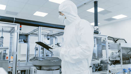 Quality Control Check: Scientist Using Digital Tablet Computer and wearing Protective Suit walks through Manufacturing Laboratory. Product Manufacturing: Pharmaceutics, Semiconductors, Biotechnology.