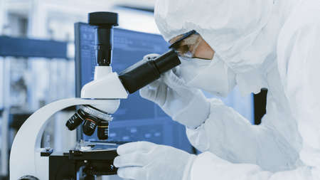 Close-up Shoy of a Scientist in Protective Clothes Doing Research Uses Microscope in Labolatory. Modern Manufactory Producing Semiconductors and Pharmaceutical Items.