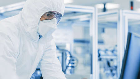 In Laboratory Scientists in Protective Clothes Doing Research, Using Microscope and Entering Data into Personal Computer. Modern Manufactory Producing Semiconductors and Pharmaceutical Items. Foto de archivo