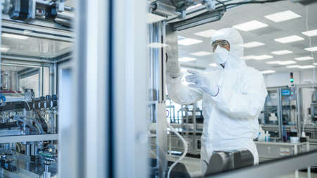 In the Manufacturing Facility Shot of Scientist in Sterile Protective Clothing Work on a Modern Industrial 3D Printing Machinery. Pharmaceutical, Biotechnological and Semiconductor Creating