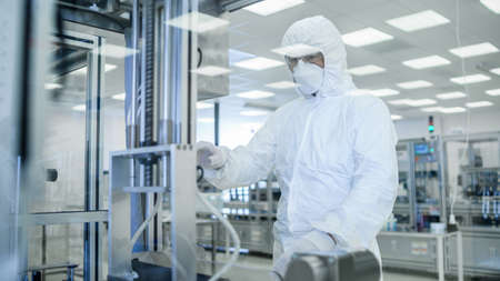 In Manufacturing Facility Shot of Scientist in Sterile Protective Clothing Work on a Modern Industrial 3D Printing Machinery. Pharmaceutical, Biotechnological Manufacturing Process. Shot from Inside. Foto de archivo