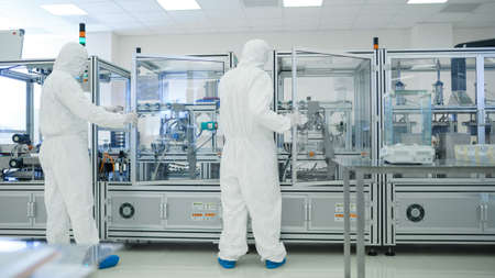 In the Manufacturing Facility Team of Scientist Wearing Sterile Protective Coverall Sets up Programs Modern Industrial 3D Printer, High Precision Manufacture of Semiconductors under Process.