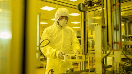 In the Manufacturing Facility Scientist Wearing Sterile Protective Coverall Sets up Programs Modern Industrial 3D Printer, High Precision Manufacture of Semiconductors under Process. Shot from Inside