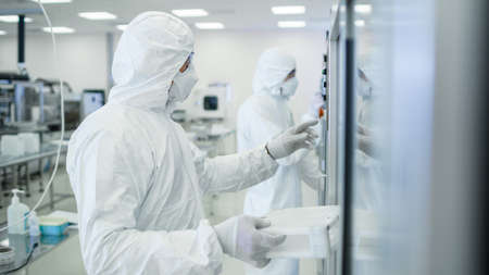 In the Manufacturing Facility Team of Scientist Wearing Sterile Protective Coverall Sets up Programs Modern Industrial 3D Printer, High Precision Manufacture of Semiconductors under Process. Foto de archivo