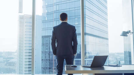 Back View of the Thoughtful Businessman wearing a Suit Standing in His Office, Hands in Pockets and Contemplating Next Big Business Deal, Looking out of the Window. Big City Business District