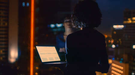 Stylishly Dressed Businesswoman Holds Laptop While Looking Out of the Window of Her Office. Late at Night Woman Doing Important Job. Window Has Big City Business District View with Many Night Lights.