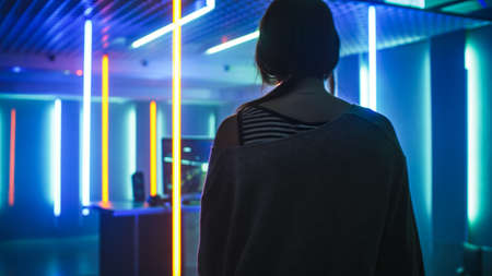 Back View Shot of the Beautiful Professional Gamer Girl Looking at Her Room in Retro Neon Lights with Her Personal Computer. Casual Cute Geek wearing Glasses.