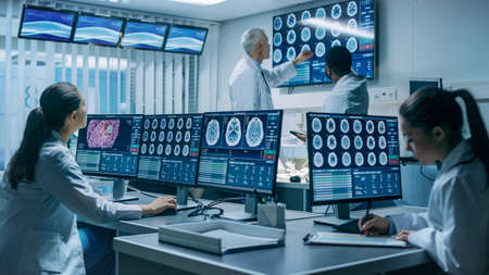 Team of Professional Scientists Work in the Brain Research Laboratory. Neurologists Neuroscientists Surrounded by Monitors Showing CT, MRI Scans Having Discussions and Working on Personal Computers.